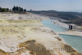 Lookout over travertine terraces and thermal pools with tourists at Pamukkale Turkey