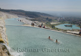 Mineral water flowing into hot spring pools depositing travertine terraces with tourists and bathers at Pamukkale Turkey