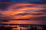 Fiery sunset at Kusadasi Turkey Harbour with Guvercin Adasi Island on the Aegean Sea with mountains of Samos Greece