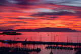 Red sky sunset at Kusadasi Turkey Harbour with Guvercin Adasi Island castle on the Aegean Sea with mountains of Samos Greece