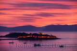 Red sky sunset at Kusadasi Turkey Harbour with lit Guvercin Adasi Island Genoese castle on the Aegean Sea with mountains of Samo