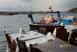 Restaurant tables at waters edge with fishing boats in harbor village of Assos Iskele Behram Turkey