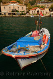 Fishing boat with hotels and police station in the hamlet of Assos Iskele or Behram Turkey