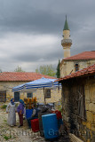 Local women talking at an olive stand in ancient hillside village of Yesilyurt Turkey with minaret