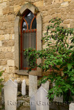 Mosque window with gravestones and pokeweed bush in hillside village of Yesilyurt Malatya Turkey