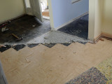Tearing out old tile under carpeted area.