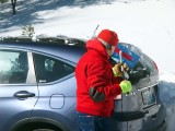 Clearing snow from the vehicle.