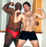 couple gay wrestlers flexing arms hairychests.jpg