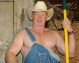 handsome cowboy man denim overalls shoveling barn.jpg