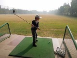 First time at a driving range.  Insisting on using Dad's clubs.