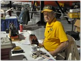 Ed Lusk sits at control table for G scale layout