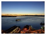 Ferry Approaches Waterfront Against a Background of a Sunset Over Elliot Bay and the Olympic Mountains