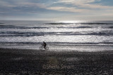 Cyclist on beach with Tasman sea backdrop