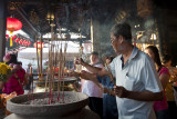 MALACCA, MALAYSIA - FEBRUARY: Devotees pray by placing joss-sticks in bronze jars placed on the altar on the first day of the Ch