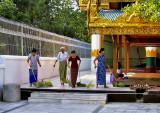 Women sweeping temple courtyard