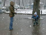 Mother and child play snowball in the first snow on Dostyk. His first year to be old enough?
