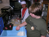 The teacher looks on as Brendon forms the rice, after cutting some tuna.