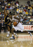 Jackets G Clinch drives into the paint past Spartans G Johnson