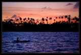 Villager paddling by at sunset