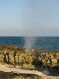 Water spurting through rocks on beach