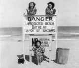 1938 - Lutrelle Conger (bottom) and friends by the unprotected beach sign on Miami Beach