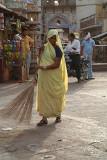 Woman in Yellow Sweeping