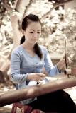 Girl playing Auld Lang Syne on a  Ðàn Bâ`u