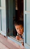 Laos boy peeking through window