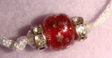 Silver colored stars on red beads-detail
