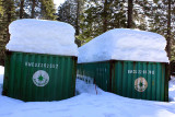 Snowshoe pole between these storage containers helps illustrate snow depth