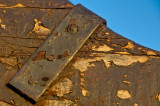 Metal with bolts and old painted wood against blue  sky