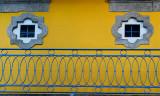 Twin windows, yellow wall, blue veranda