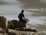 A surfer waits for his friend at Praia do Rosa Beach in Santa Catarina, Brazil