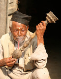 Smoking a Nepali pipe.