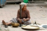 Lady pounding rice, Nepal.