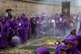 The purple clad cucuruchos march beside many alfombras