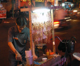 Street vendor with roasted squids, Saigon