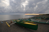 Fishing boats on the beach with clouds and rain blocking sunset