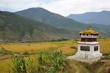 A stupa with prayer wheels set among the rice fields