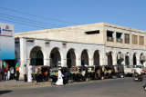A line of tuk-tuks in front of an arcade, Port Sudan