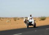 Sudanese man riding a donkey cart sidesaddle along the main road