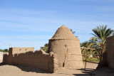 Mud brick wall and round building