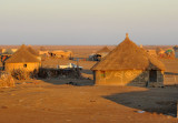 Village of thatched rondavels on the flat desert of Eastern Sudan