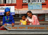 An old Nepali woman smiles as a little girl on a passing bus waves