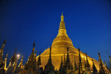 Gold of the main stupa of Shwedagon Paya standing out against a deep blue evening sky