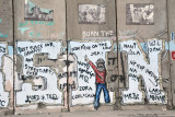 West Bank Separation Wall graffiti - Palestinian youth giving V sign