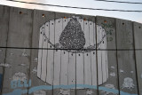 West Bank Separation Wall graffiti - Christmas tree encircled by the Wall with tree stumps, Bethlehem