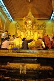 Devotees adding gold leaf to the Mahamuni image