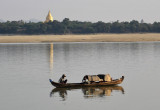Small boat on the Irrawaddy River with the gold-covered stupa of Shwezigon Paya