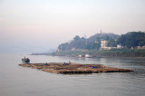 Large bamboo raft being towed down the Irrawaddy River past Sagaing